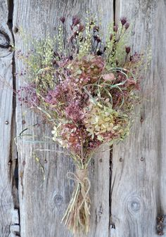 Dried flower bouquet handcrafted from beautiful mixed color small bunches of Hydrangeas, zebra grass from my garden with pretty burgundy dyed wild pods , pink dyed yarrow and meadow grasses and pepper grass from a farm. Size: approx. 22 x 10 This a floral arrangement designed as a bouquet to be enjoyed as home decor, special event.  ***Natural Dried Flower Bouquets, and Floral Arrangements cannot be returned because they are delicate and may not handle being shipped more than once without…
