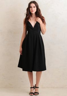 This elegant black midi dress is perfect for creating a classic feminine look. It's designed with a flattering V-cut neckline, a hidden back zipper, and a voluminous skirt with box pleati...