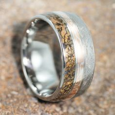 This Dinosaur Bone and Meteorite Wedding Band is accented by a thin Mokume Gane pinstripe to give it that sophisticated look. The Dinosaur Bone and Meteorite inlay is solid and goes all the way around the Titanium Ring. The Mokume Gane pinstripe brings the two together with a unique touch. [...]