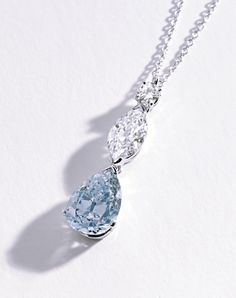 PLATINUM, FANCY INTENSE BLUE & NEAR COLORLESS DIAMOND PENDANT-NECKLACE.  The pendant set with a pear-shaped diamond of fancy intense blue color weighing 2.59 cts, surmounted by a marquise-shaped diamond .92 ct, & a round diamond approx .10 ct, completed by a platinum, link chain, length 17½ inches.