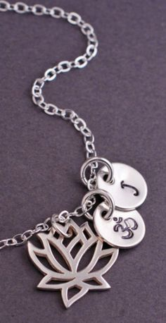 A sterling silver lotus flower measuring 5/8 inch is paired with optional charms. Chain is available in 16, 18, 20, 24, and 30 inches. **ALL CHARMS ARE OPTIONAL. Choose from stainless steel initial ch