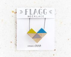 NECKLACE WITH GEOMETRIC DESIGN. BIRCH WOOD PAINTED BY HAND The necklace Flagg is handmade with three hand-painted wooden cubes. It is inspired by the nautical flags (Flagg means Flag in Swedish)  Our necklaces are made with wood from sustainable forestry and water based inks.  COLORS: There are two color combinations. Choose your favourite one! ▲ Mustard yellow + Grey + Blue ▲ Mustard yellow + Grey + Orange  SIZE: 10,8″ x 1,39 (27,4 x 3,53 cm)  You can see more Olulas products here…