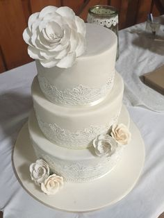 A stunning wedding cake for a lovely couple. Simplicity in ivory and white detailing and a rustic setting
