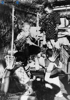 名古屋郊外の農家の子供たちは、親が市場へ出荷する大根を、オヤツに食べている。1947年11月26日