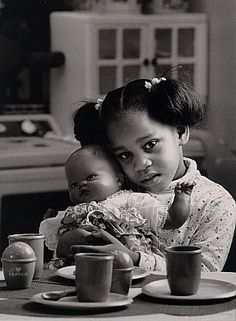 Playing House  Action For the Homeless. Black & white location photographic portrait of female child with doll in community shelterl