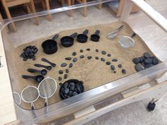 Invitation in the sand table - strainers, measuring cups and spoons and black stones. Sensory Tubs, Sensory Activities, Sensory Play, Preschool Activities, Play Based Learning, Learning Through Play, Early Learning, Sand And Water Table, Sand Table