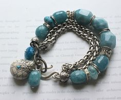 blue chalcedony stones, with two strands of chunky woven silver link chain, and barrels of faceted blue chalcedony, crystal spacers, wheels of blue faceted quartz, silver caps and a center of three large multi faceted nuggets of blue chalcedony, with wrap beads between, with three drops off the back, a crackled white sterling silver tibetan charm, a barrel of chalcedony, a wheel of blue quartz, measuring 8 inches and I can easily adjust unique handmade bracelet, by Mollie Carey~<3