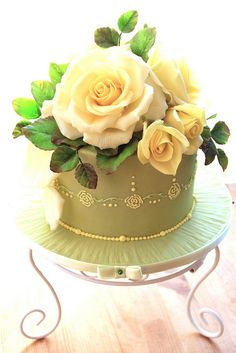 Chocolate and orange cake enrobed in white chocolate fondant and adorned with yellow gumpaste roses.