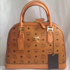 MCM signature bowler bag Brand new with tags MCM bag in classic tan signature logo. Super hot brand right now! Easy to carry bag , never been used! Comes with tags and dust bag authentic! Luxury Purses, Luxury Bags, Mcm Bags, Purses And Bags, Mcm Shoes, Louis Bag, Micheal Kors Handbag, Cute Luggage, Mcm Backpack