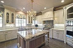 Traditional luxury kitchen with antique white cabinets, chandelier, granite island and mosaic backsplash