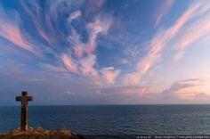 La croix de Saint-Gildas-de-Rhuys face à l'océan - Sur la pointe du Grand Mont se dresse une croix en pierre, plantée au sommet de la falaise. Elle domine la mer, sous un ciel de crépuscule aux nuages teintés de rose. Presqu'île de Rhuys, Morbihan (Bretagne, France)