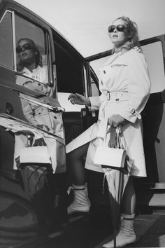 Ursula Andress wearing sunglasses, a white raincoat and boots, as she prepares to enter a car upon her arrival at London Airport 1965 ndress had arrived for wardrobe fittings for the film 'The Blue Max' Getty Archive Ursula Andress, London Airports, Come Fly With Me, Raincoats For Women, Iconic Women, Airport Style, Hades, Bikini Models, Old Women