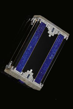 An Art Deco lapis lazuli, rock crystal, enamel and diamond cigarette case, probably BOUCHERON, 1920s. The base and lid applied with lapis lazuli and black enamel, millegrain-set with synthetic sapphires, baguette and rose diamonds, the rock crystal sides carved with floral motifs, with carved lapis lazuli push-buttons, unsigned, fitted case Boucheron, Paris, further accompanied by suede travelling case.