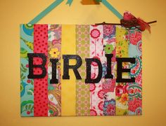 Patch work strips of fabric on a canvas with Birdie's name in black glitter...