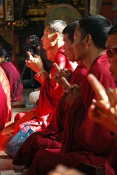 Red reflects on monks with hands in mandala prayer mudra, Lamdre dedication of merit, camera tripod, drum, Tharlam Monastery of Tibetan Buddhism, Boudha, Kathmandu, Nepal