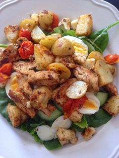 Healthy lunch recipe. Herby chicken, soft boiled egg, new potato, roasted tomatoes and spinach salad with halloumi cheese.