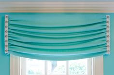 "Simple window treatments seem inspired by waves. ""I wanted them to be simple, and I didn't want them to contrast with the walls,"" says Corbet, who fashioned valances from a Pindler & Pindler linen trimmed in studded leather. Roller shades tucked behind the valance help control the light. (contemporary  by Kathy Corbet Interiors)"