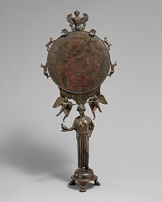 Her mirror: Bronze mirror with a support in the form of a draped woman Period: Classical Date: mid-5th century B.C. Culture: Greek, Argive Medium: Bronze Dimensions: H. 15 15/16 in. (40.41 cm) Classification: Bronzes Credit Line: Bequest of Walter C. Baker, 1971 Accession Number: 1972.118.78