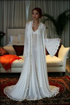 Sarafina Prima is our higher end line and this robe is from our latest collection. Silks, satins and exclusive laces tailored for the clientele who is used to the best and perfectly suited for the elegant bride.  The Sophie robe drapes the body in the absolute softest veil of fabric. A delicious stretch French netting in a pale ivory with just a hint of blush. A mix of femininity, romance and definitely sensuality.  A fluid cloud swirls around you when you walk, wide angel sleeves perfect to…