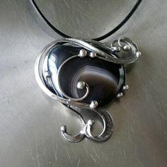 Blossom ( achát ) Náhrdelník z achátového kabošonu (Botswana) -zdobený cínem technikou Tiffany a drátem. Patinováno,ošetřeno antioxidantem,broušeno,leštěno. Přívěsek ovelikosti 5,5 x 5 cm je zavěšen na kulaté kůži se zapínáním na karabinku,délka - obvod cca 48 cm. Na cínování polodrahokamů používám atestovaný bezolovnatý cín. Pokud si přejete změnit ...