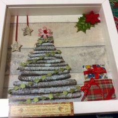 Quadre emmarcat. L'arbre està fet de troncs, els regalets del costat de roba , les estrelles i flors són guarniments de Nadal.