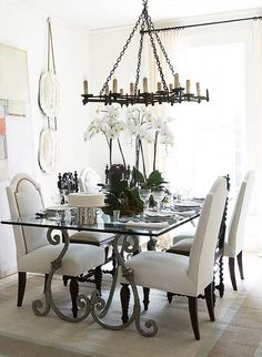 Distinctive furnishings in a white dining room. LOVE how the large piece of art leans against the wall.