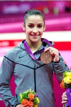 U.S. gymnast Aly Raisman poses with her bronze medal from the London Olympics' women's gymnastics balance beam event final.
