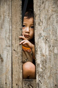 A child is glancing through a gap in the wall of a daycare at the #refugee camp Mae Ra Ma Luang in #Thailand.  By Christian Bobst
