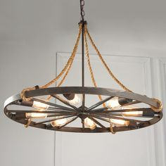 "Vintage Wagon Wheel Chandelier  We take wood and metal wagon wheels from the past, add rope details, and alternate regular sockets between every other spoke for a chandelier that really has a style story to tell! 8x25 watts medium sockets. (31""Hx24""W) 5"" round canopy. $449"