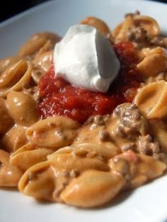 Taco Macaroni and Cheese... 1 pound macaroni or shell pasta 1 pound ground beef 1 onion, chopped 2 cloves garlic, minced 1 serving of taco seasoning (or 1 packet of store-bought seasoning mix) 1 cup salsa 1 8-ounce package cream cheese, cut into chunks 2 cups milk 1/2 cup sour cream 2 cups shredded Mexican cheese blend