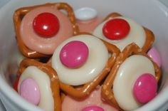 Valentine's Day treats-pretzel snaps, white or pink chocolate melting discs, M oven to 350 degrees.  Place pretzels right side up on a baking sheet. Place a chocolate disk on each and carefully place in the oven for 2 minutes, just long enough for the chocolate to begin to melt. Pull the tray out of the oven and quickly press one M onto the center of each chocolate disk. Put the tray in your garage or fridge to set.