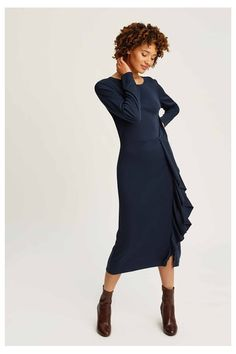 This light and fluid dress has a round neckline with a drawn in waist that's framed by elegant and flattering ruffles. The sleeves are slim and this style looks best worn with tights and ankle boots.