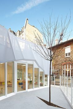 Nursery extension in Paris by h2o Architectes enveloped by a folded fabric sunshade