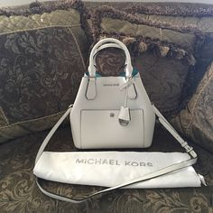 """Michael Kors Greenwich large grabbag Michael Kors Greenwich large grabbag   -Magnetic snap tap closure and cutout logo MK charm and name plate on bag -Main pocket, exterior snap pocket and interior zip pocket -Saffiano leather  -11""""W x 11""""H x 7""""D -5"""" strap drop; 18 ½"""" - 21"""" shoulder strap drop. -Color: opwht/aquamarine   Bag is in great condition. Only flaw is some minor scuffs of bottom of bag and some scuff on the back of the bag where the right handle begins. Not noticeable. Refer to…"""