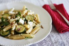 Penne with zucchini, chilli flakes & feta cheese - 350g pasta; 20ml olive or grapeseed oil; 3 large zucchini, sliced; 2 garlic cloves, crushed; A pinch dried chilli flakes; 100g feta cheese, crumbled; 1/2 lemon, juiced (around 30-40ml); 1t grated lemon rind; 1/3C chopped continental parsley; Around 30g toasted nuts of your choice – I recommend pine nuts or chopped walnuts.