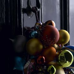 Instead of hanging a wreath, round up a few ornaments (preferably shatterproof and/or ones you don't mind having knicked and scratched) and tie them to a nail or door knocker. We're thinking this idea would look even lovelier topped with a large, simple bow.