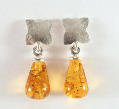 Wunderschöne Bernsteintropfen-Ohrringe aus 925er Silber. Die Tropfen schaukeln an einer aufgetieften Schale und sind poliert. Oben habe ich ein stilisiertes Blümchen entworfen, das etwas aufgetieft...