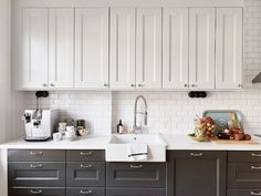 black and white kitchen with white top cabinets and black bottom
