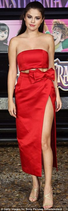 Thigh's the limit: She showcased her fab figure in a shiny red two-piece number featuring a very thigh-high split