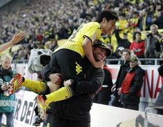 Dortmund's Shinji Kagawa of Japan, top, and Dortmund head coach Juergen Klopp celebrate after scoring during the German first division Bundesliga soccer match between Borussia Dortmund and Borussia Moenchengladbach in Dortmund, Germany, Saturday, April 21, 2012.