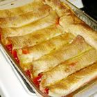 "Cherry Enchiladas.....""Cherry Pie like you've never had it before! Cherry pie filling wrapped in flour tortillas, soaked overnight in a sweet liquid, then baked. I used to work at a bed and breakfast, and we would make this sometimes for catered luncheons. I added my own touch with the almonds."""