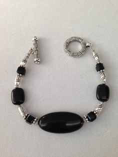 This bracelet is made of black beads with silver spacers and clasp. Matching earrings available. You can view more of my jewelry and gift