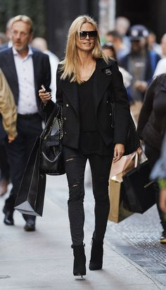 Heidi Klum stuns in head-to-toe black. She wears shades, a jacket, ripped jeans, and heeled booties which evoke a dauntless attitude.