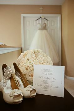 Dress, shoes, bouquet, and invitation. Wedding photography.