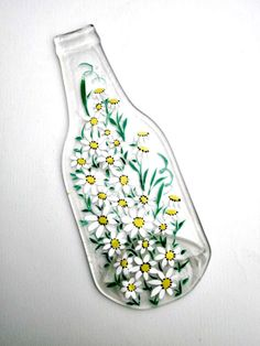 Clear beer bottle melted into a great spoon rest/ Trivet. Or add a votive candle and you get a great decoration.  It has been hand painted with white daisies. The paint has been heat set but will last longer if it is hand washed. Great housewarming gift. Or a wedding gift.  Recycled is always great.  See more spoon rests.https://www.etsy.com/shop/GlassGaloreGal?section_id=11266793