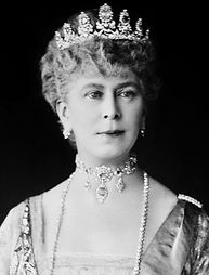 Cambridge Sapphire Tiara  Originally this tiara was of a diamond prong design with sapphires at the top. Now it is a grouping of sapphire and diamond flowers set on a velvet band. It was first given to the Grand Duchess Augusta of Mecklenberg-Strelitz, Duchess of Cambridge who married Prince Adolphus, Duke of Cambridge; son of King George III of the United Kingdom. Her granddaughter, Queen Mary (above) inherited it.