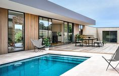 Minimalist beach house with wooden slat exterior and black accents and pool #modernpoolandspa