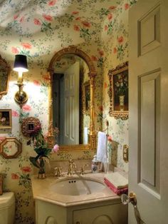 This powder room is so charming. I love the wallpapered ceiling, the little wall sconce and mirror