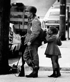 Two little girls peek into the pack of a national guardsman on duty in Wilmington, Delaware, as calm settles over the city after riots following the assassination of Martin Luther King, Jr, April 11, 1968 - namraka:Original caption: Two little girls peek into the pack of a national guardsman still on duty in Wilmington, Delaware, on April 11, 1968, as calm settles over the city after two days of looting, burning and stoning. (AP Photo)