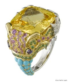 Van Cleef & Arpels  Makara Ring  White gold, round diamonds, yellow gold, turquoises, mauve and pink sapphires, peridots, one 30.76-carat cushion-cut yellow (from Sri Lanka)    The central stone of the ring is a yellow sapphire with a golden glow and represents the colourful, festive world of the Oriental Ball. As all Van Cleef & Arpels' stones, this extremely pure gem of 30.76 carats has never been heated or artificially treated. On several parts of the mounting, particularly on the…